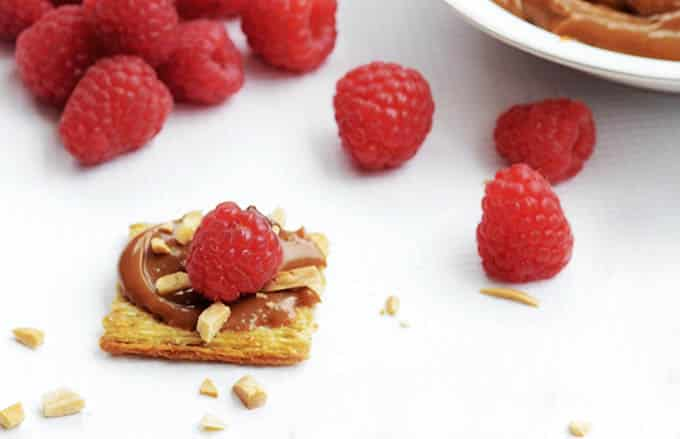Salted Caramel and Raspberry Triscuit Squares! A salty sweet combo of Raspberries filled with chocolate, salted caramel and toasted almonds on top of Triscuits! A yummy appetizer! #TriscuitSnackoff