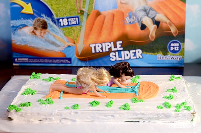 Picture of cake with waterslide decoration and dolls on top to look like they are sliding.