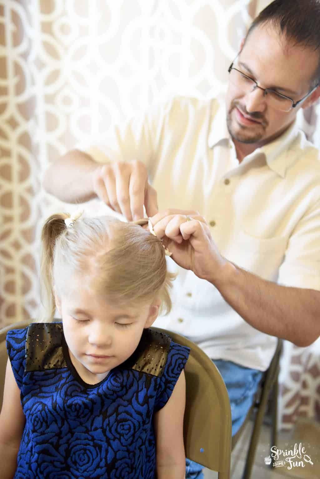 Dad making pigtails in girls hair
