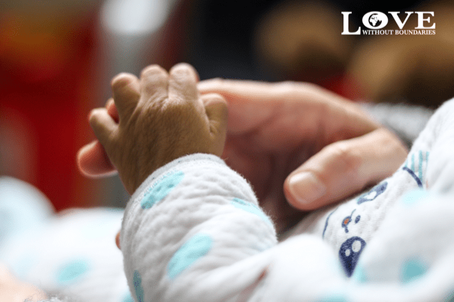 Picture of tiny baby hand in an adult hand.